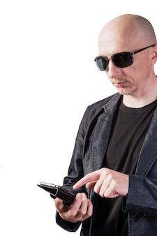Un homme vêtu d'une veste en jean portant des lunettes de soleil compose un numéro sur un smartphone