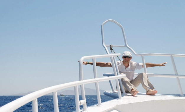 Un homme vêtu de vêtements lumineux portant une casquette et des lunettes sur un yacht est heureux de partir