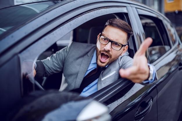 Un homme vêtu vif se retrouvant pris dans une heure de pointe et succombant lentement à la rage au volant.