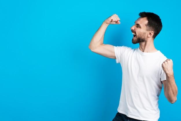 Homme victorieux posant avec les biceps