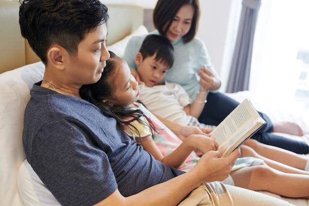 Homme vietnamien lisant un livre intéressant pour ses enfants et sa femme lorsqu'ils sont tous allongés sur le lit