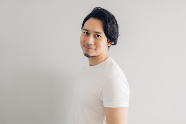 Homme de visage de sourire heureux aux longs cheveux noirs et t-shirt blanc.