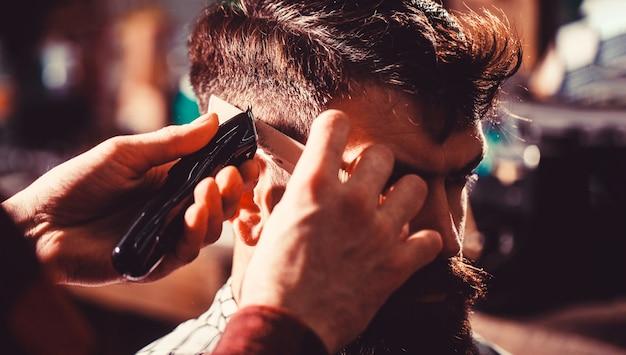 Homme visitant un coiffeur dans un salon de coiffure. le coiffeur travaille avec la tondeuse à cheveux