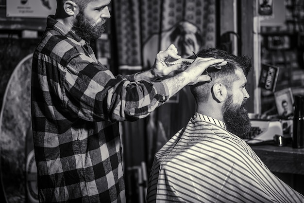 Homme visitant le coiffeur en salon de coiffure. ciseaux de coiffeur. noir et blanc. homme barbu en salon de coiffure.