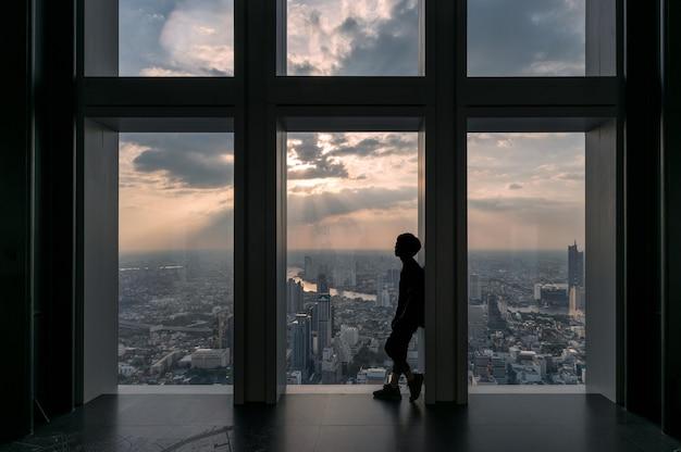 Homme visitant la ville au-dessus du bâtiment par des fenêtres au coucher du soleil