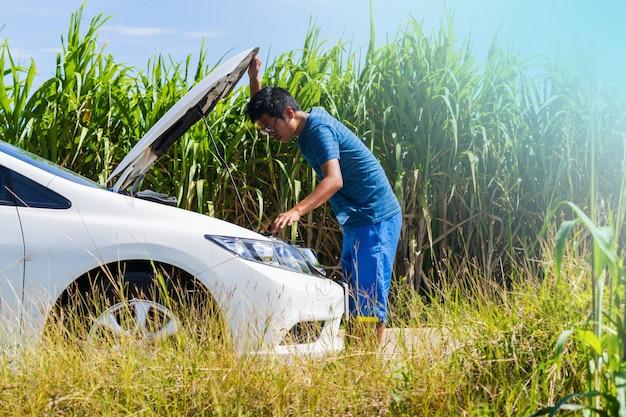 Un homme et une voiture blanche à problèmes sur la route