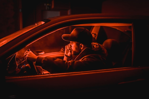 Homme en voiture fumer la nuit dans un garage éclairé par un feu rouge