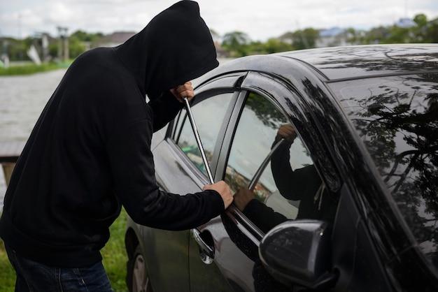 Homme voleur utiliser crowbar pour briser le verrouillage de la voiture