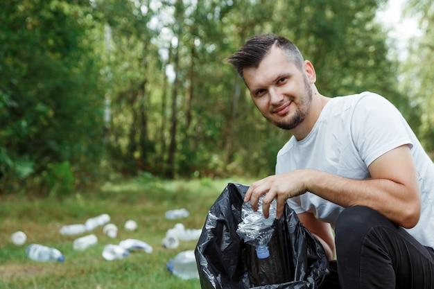 Un homme volontaire tenant un sac à ordures ramasse du plastique.