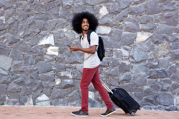 Homme de voyage souriant avec téléphone et sacs à pied à l'extérieur