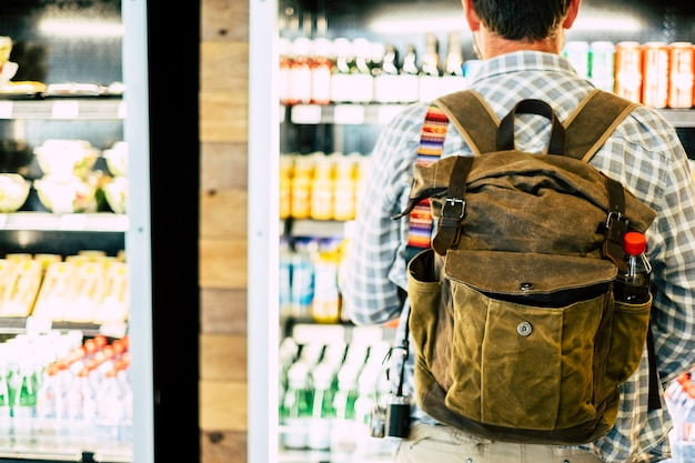 Homme de voyage vu de dos devant un magasin de boissons automatique choisissant des collations ou des boissons avant de partir ou de commencer le voyage d'affaires ou de vacances - vue de l'arrière sur le sac à dos