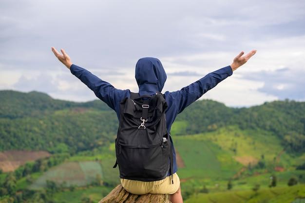 Un homme voyageant appréciant et relaxant sur la belle vue sur la montagne verte en saison des pluies, climat tropical.