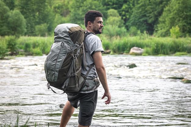 Un homme voyageant avec un grand sac à dos de randonnée se tient près de la rivière.