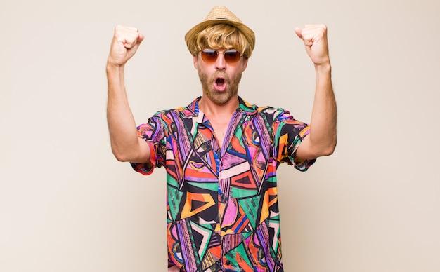 Homme voyageur adulte blonde célébrant un succès incroyable comme un gagnant, l'air excité et heureux