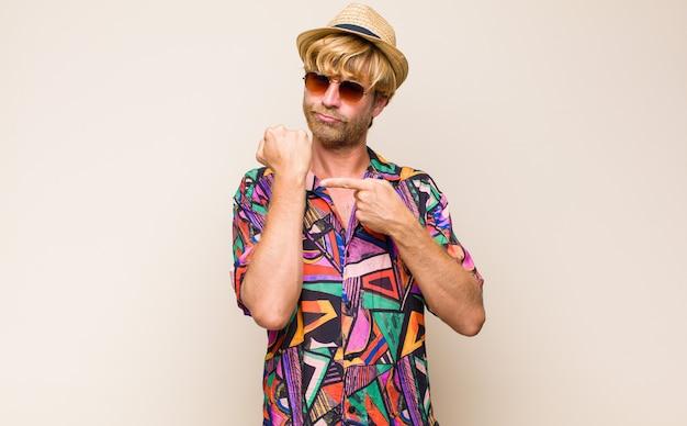 Homme voyageur adulte blonde à la recherche d'impatience et en colère, pointant sur la montre, demandant la ponctualité, veut être à l'heure