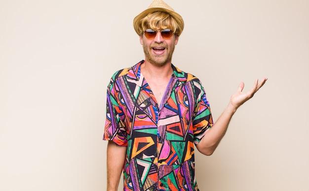 Homme de voyageur adulte blonde se sentant heureux, surpris et joyeux, souriant avec une attitude positive, réalisant une solution ou une idée