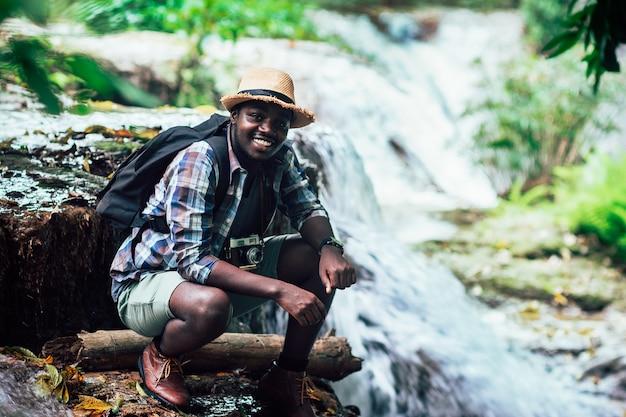 Homme de voyageur africain assis et relaxant liberté avec cascade