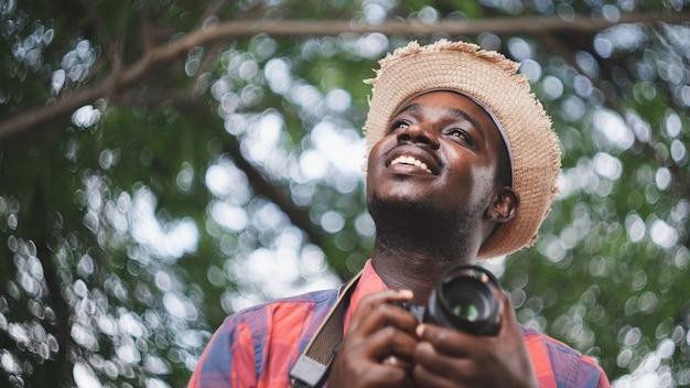 Homme de voyageur africain tenant un appareil photo dans le fond de la nature verdoyante