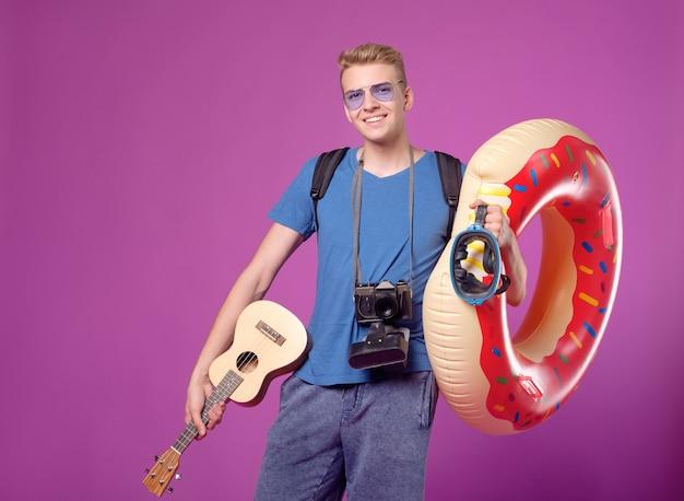 Homme voyageur avec caméra, cercle de natation et ukulélé guitare sur fond violet