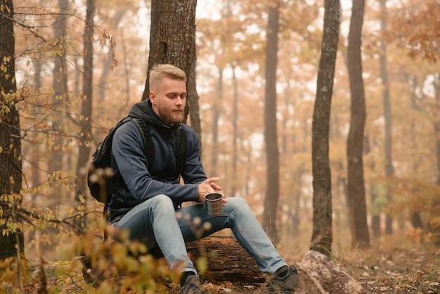 Un homme voyageur dans la forêt d'automne se repose sur une halte et boit du thé.