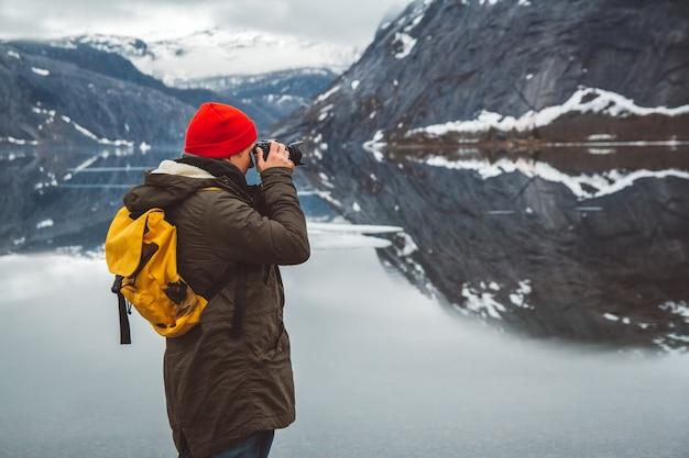 L'homme voyageur debout sur le fond des montagnes et du lac fait un paysage photo