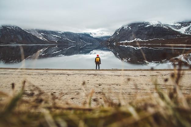 Homme de voyageur debout sur le fond des montagnes et du lac profitant du paysage dans les lofoten en norvège
