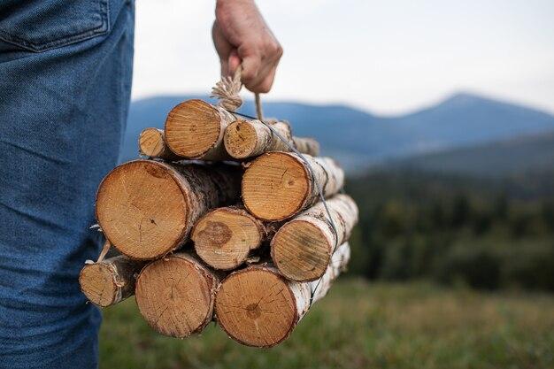 Homme voyageur mains tenant du bois de chauffage pour le feu dans les montagnes. lieu d'inscription.