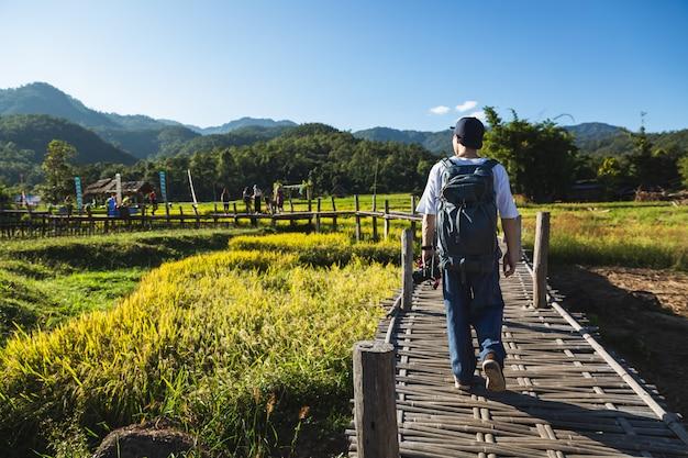 Homme voyageur marchant sur un pont dans les champs de la nature