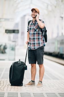 L'homme de voyageur parle au téléphone à la gare