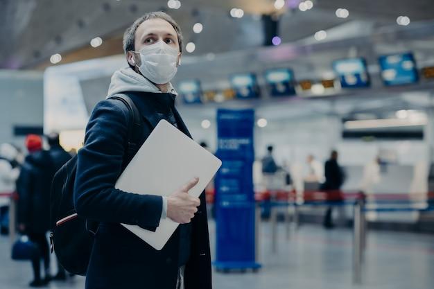 Un homme voyageur porte un masque médical jetable à l'aéroport, revient de l'étranger où le coronavirus se propage, porte un sac à dos, prend soin de sa santé, protège contre les virus, a reporté son vol