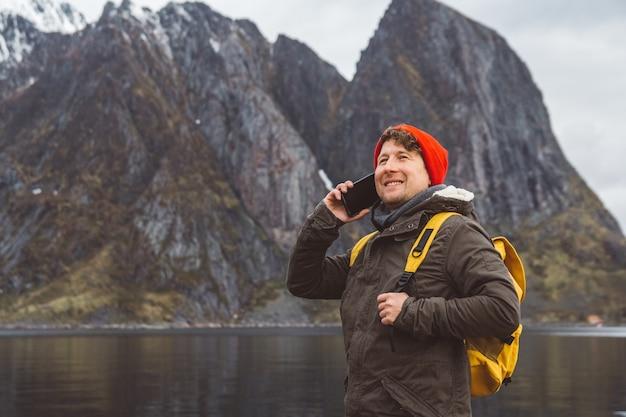 Homme de voyageur de portrait parlant au téléphone portable se tenant sur un fond d'une montagne et d'un lac