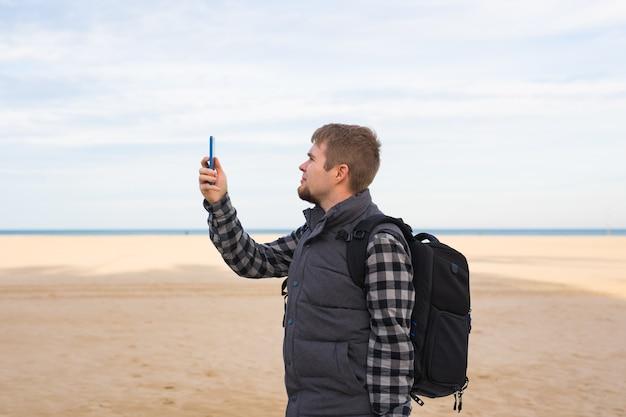 Homme voyageur prenant des photos à la plage avec smartphone