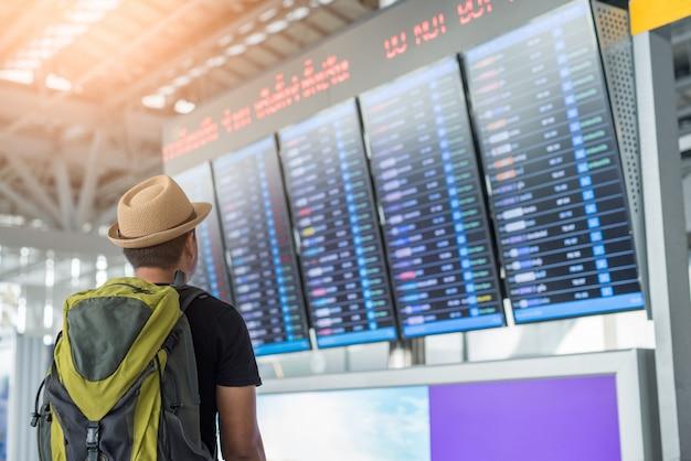 Homme voyageur à la recherche d'horaires de vol à l'aéroport.