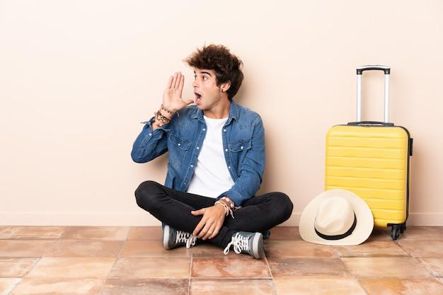 Homme voyageur sa valise assis sur le sol en criant avec la bouche grande ouverte