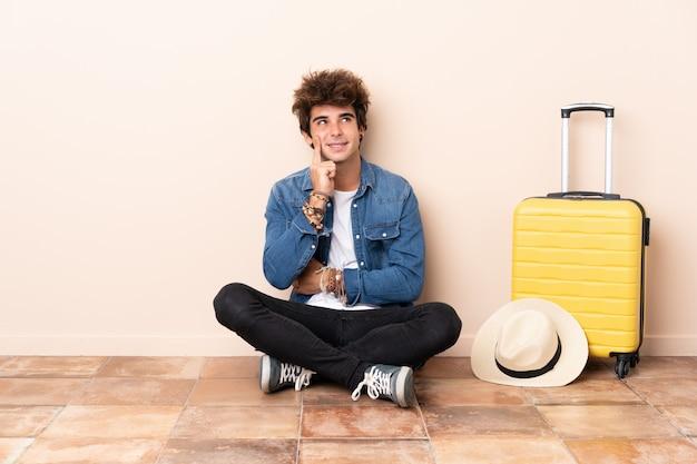 Homme voyageur sa valise assis sur le sol en pensant à une idée