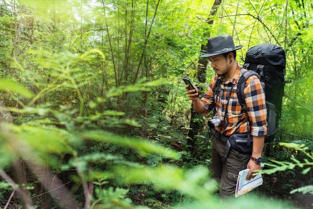 Homme voyageur avec sac à dos à l'aide de smartphone dans la forêt
