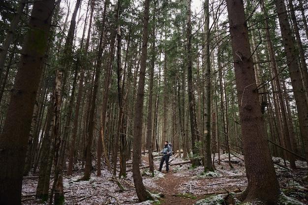 Homme voyageur avec sac à dos debout dans la forêt