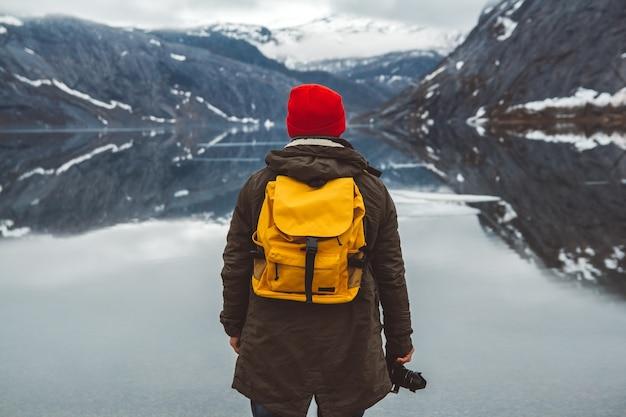 Homme de voyageur avec un sac à dos debout sur le fond des montagnes et du lac, profitant du paysage