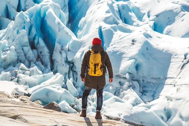 Homme de voyageur avec un sac à dos debout sur un rocher sur fond de montagnes glaciaires et de neige