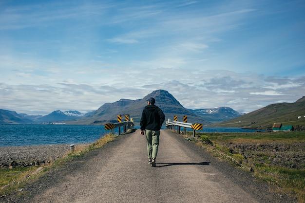Un homme voyageur avec sac à dos explore l'islande