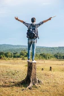 Un homme voyageur avec un sac à dos, portant une carte et debout sur une souche d'arbre