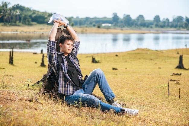 Un homme voyageur avec un sac à dos portant une carte et s'appuyant sur une souche d'arbre.