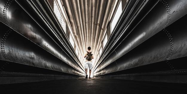 Homme voyageur solitaire avec sac à dos marchant dans un tunnel urbain en acier