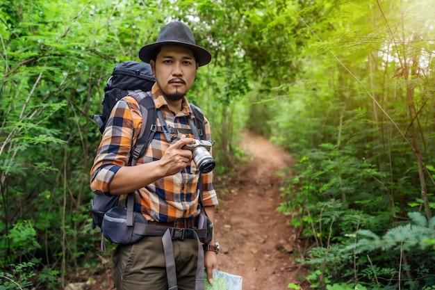 Homme voyageur tenant la caméra avec sac à dos debout dans la forêt