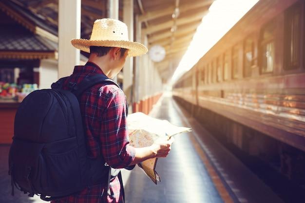 Homme voyageur tenant la carte et sac à dos en attendant le train