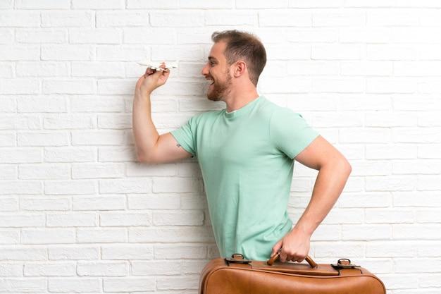 Homme voyageur avec valise sur mur de briques et courir vite