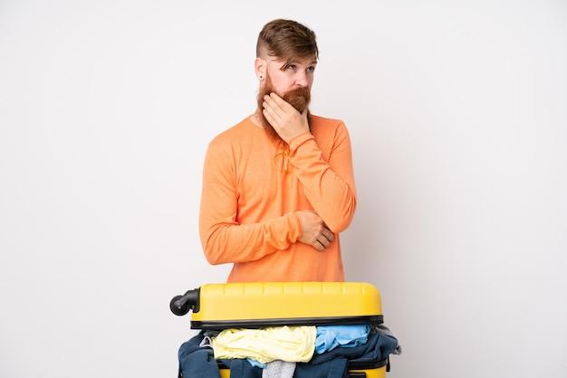 Homme voyageur avec une valise pleine de vêtements sur un mur blanc isolé en pensant à une idée