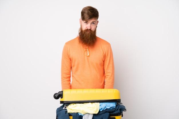Homme voyageur avec une valise pleine de vêtements sur le mur blanc isolé triste