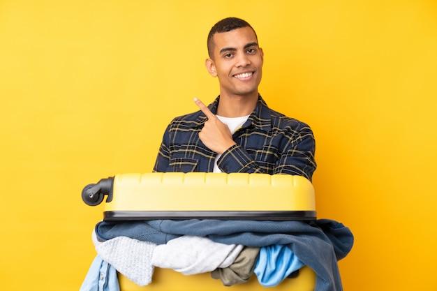Homme voyageur avec une valise pleine de vêtements sur le mur jaune isolé pointant le doigt sur le côté