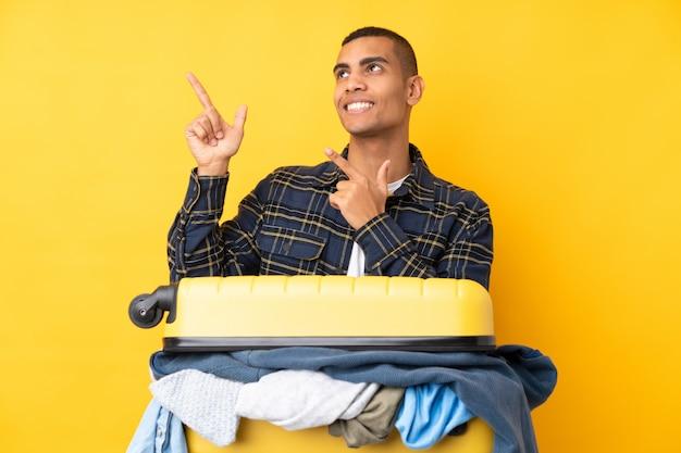 Homme voyageur avec une valise pleine de vêtements sur le mur jaune isolé pointant avec l'index une excellente idée